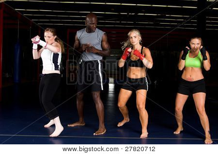 Three beautiful young woman fighters working with their trainer in an MMA gym
