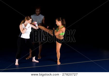 Young female MMA fighters working on high head kicks with their personal trainer in the gym