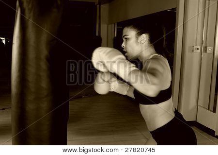 Dedicated young female fighter throwing a flurry of punches on the heavy bag Motion blur on her hands