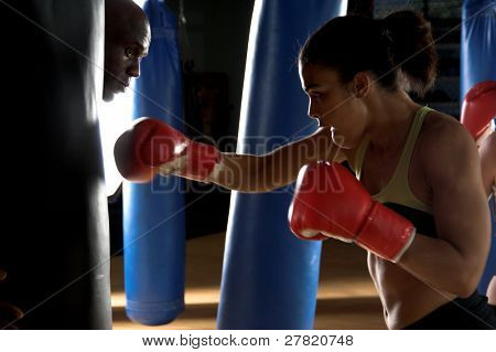 Serious female boxer throwing a right cross at the heavy bag being held by her trainer while he looks around the bag