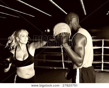 Beautiful blond female boxer in the ring throwing a right cross at the focus mitts with her trainer