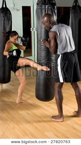 Female kick boxer kicking the heavy bag while her trainer watches