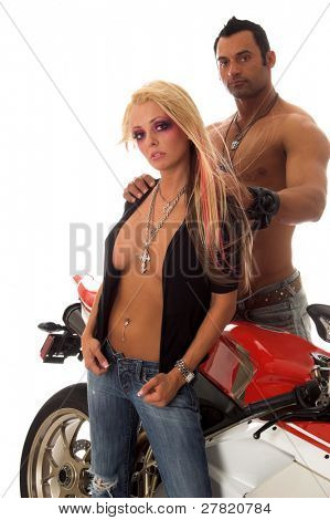 Sexy couple standing in front of a motorcycle, man with hands on woman's shoulders