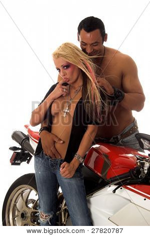 Sexy couple standing in front of a motorcycle
