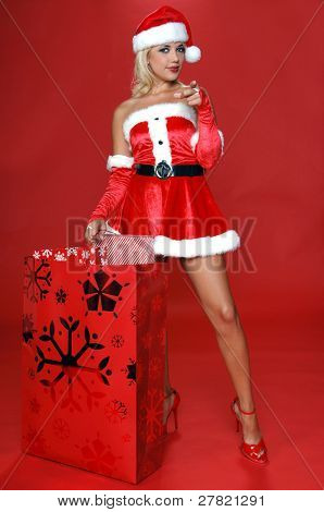 Sexy Mrs Santa with a large bag full of Christmas gifts points her finger at the viewer