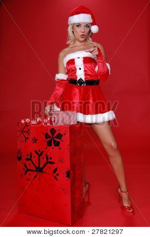 "Sexy Mrs Santa with a large bag full of Christmas gifts points her finger at the viewer and mouths the word ""you"""