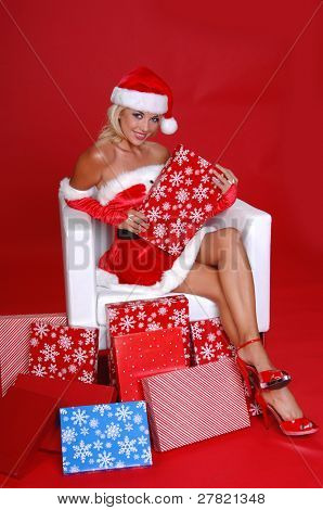 Sexy Mrs Santa Clause sitting in a snow white chair surrounded by Christmas gifts
