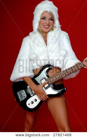 Blond snow bunny in a white furry coat and hat and black hot pants over a red background with an electric guitar