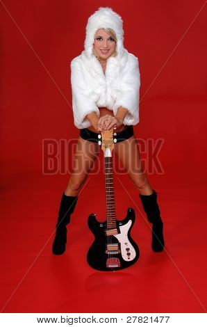 Sexy blond snow bunny in a white furry coat and hat and black hot pants over a red background with an electric guitar