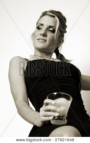 Low angle view of a young woman in a black cocktail dress with a drink sitting on a shelf in a stairway landing