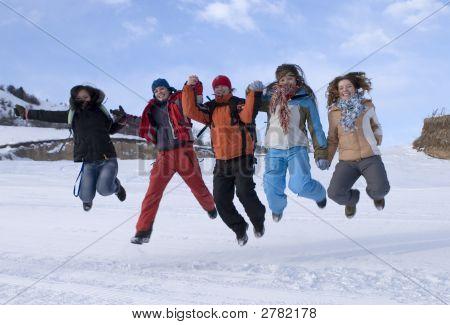 Grupo de adolescentes de esportes pulando nas montanhas, céu azul