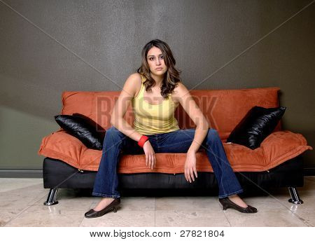 Pretty young Mexican woman in jeans and a yellow wife beater casually sitting on a black and orange couch
