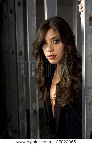 Beautiful and hip young brunette fashion model with long feathered hair and wearing Elephant Bell bell bottoms sitting in the window of a steel stud framed wall on a construction site.
