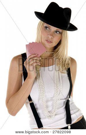 Joven rubia en ligas y un sombrero de fieltro jugando sus cartas cerca de su pecho