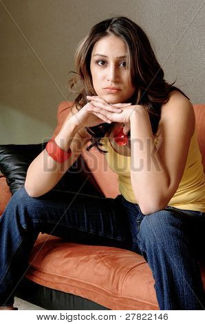 Pretty young Mexican woman in jeans and a yellow wife beater casually sitting on a black and orange couch with her chin on the back of her hands
