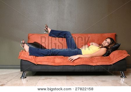 Pretty young Mexican woman in jeans and a yellow wife beater casually laying on a black and orange couch