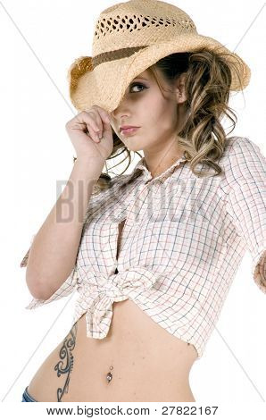 Sexy young cowgirl in a checkered blouse and straw cowboy hat