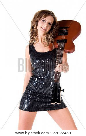 Sexy young glam rock guitarist in a black sequin mini dress and silver high heels with an electric guitar over her shoulder