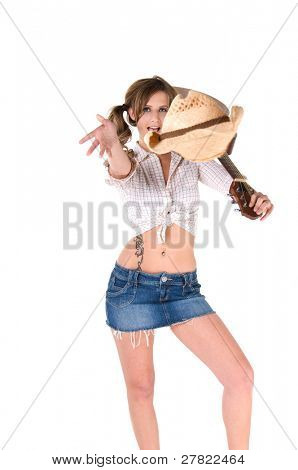 A sexy young barefooted cowgirl with pigtails smiling with a guitar over her shoulder and throwing her hat to the crowd