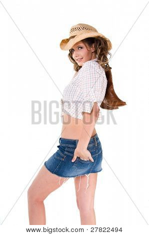 A sexy young barefooted cowgirl with pigtails smiling and holding her boots over her shoulder