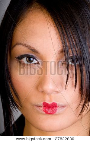 Close up of a beautiful Asian girl showing her cat eye makeup and red butterfly lips
