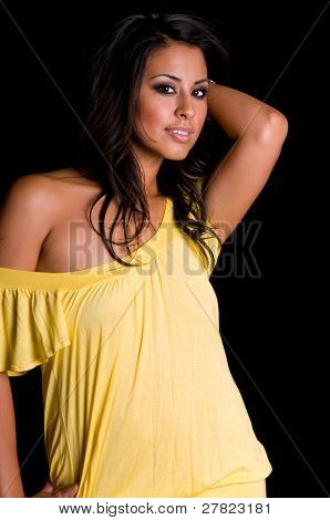 beautiful multi ethnic woman of Asian and Hispanic descent wearing a yellow dress on a black background