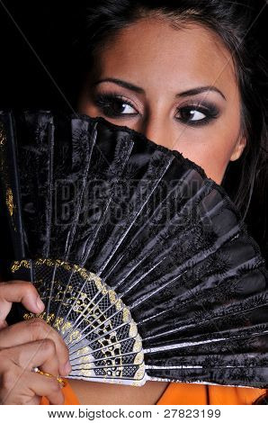 beautiful multi ethnic woman of asian and hispanic descent behind a black fan on a black background