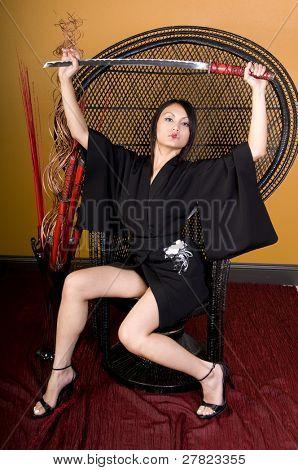 young brunette woman in Asian attire holding a samurai sword