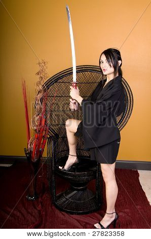 young brunette woman in Asian attire holding a samurai sword