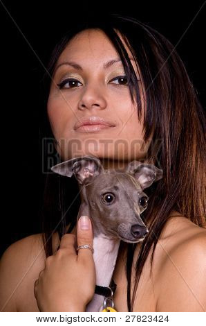 Beautiful young multi-racial woman in a black evening gown sitting on a black background and holding her pet Italian Greyhound