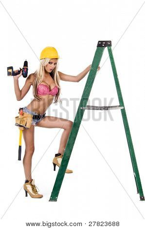High fashion glamour model in Daisy duke shorts, tool belt, pink bra and yellow hard hat with a screw gun and high heel work boots
