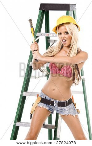 High fashion glamour model in Daisy duke shorts, tool belt, pink bra and yellow hard hat on a ladder with a hammer