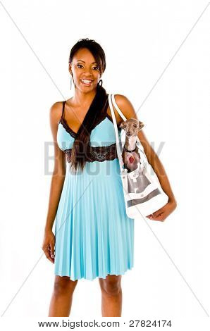 Beautiful young black woman wearing a blue dress and carrying a small dog in a shoulder bag