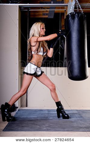 Sexy blond female MMA fighter training in the gym punching the heavy bag