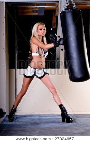 Sexy blond female MMA fighter training in the gym punching a heavy bag