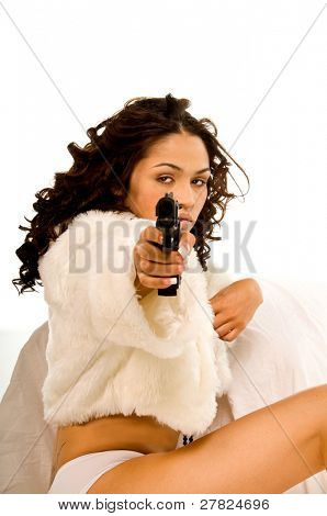 Sexy young multi-ethnic woman wearing white panties and an open white fur shrug sitting with a pistol in her hand