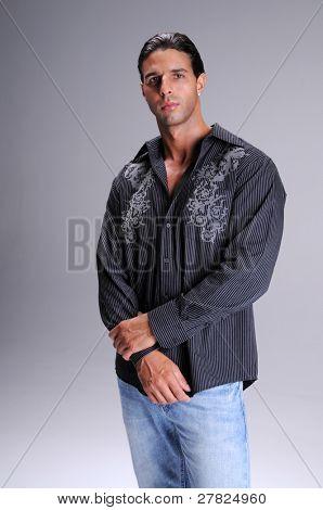 Muskulösen jungen Mann in Jeans und einem schwarzen Langarm Hemd Shirt Hals Tee stehen