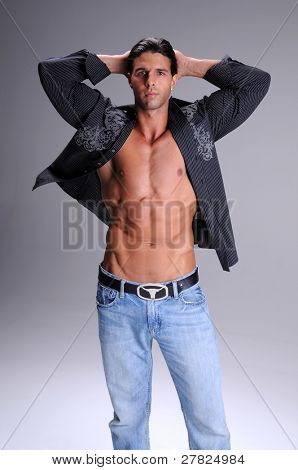 Muscular young man standing in jeans and an unbuttoned black long sleeve dress shirt neck tee shirt with his arms raised behind his head