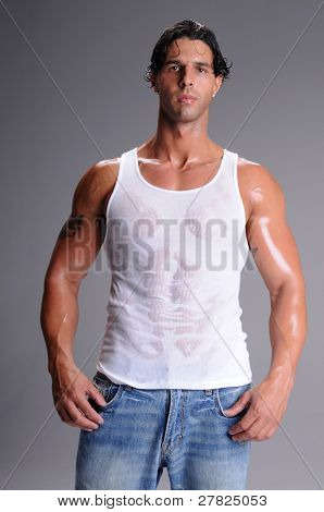Muscular young man standing in jeans and a white wife beater tee shirt