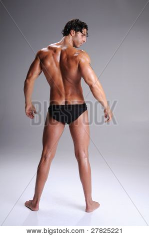 Rear view of a muscular young man standing bare chested in black brief style underwear