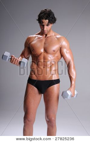 Muscular young man shirtless in briefs and sweaty working out lifting weights