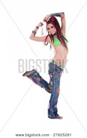 Heavily tattooed young hippie woman in retro patchwork jeans and bikini top with long red dreadlocks