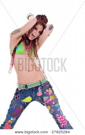Heavily tattooed young hippie woman in retro patchwork jeans and bikini top with long red dreadlocks dancing