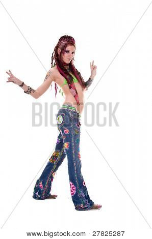 Heavily tattooed young hippie woman in retro patchwork jeans and bikini top with long red dreadlocks giving the peace sign