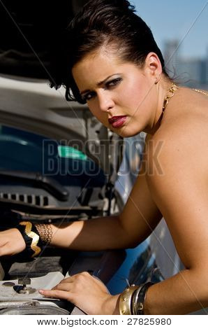 Beautiful young Italian woman stranded along the road with a broke down car wearing a fashionable black and gold party dress