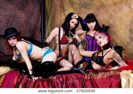 Gesindel mitreißende Gruppe von burlesken Puppen Tänzerinnen versammelten sich auf dem Bett ihre Garderobe
