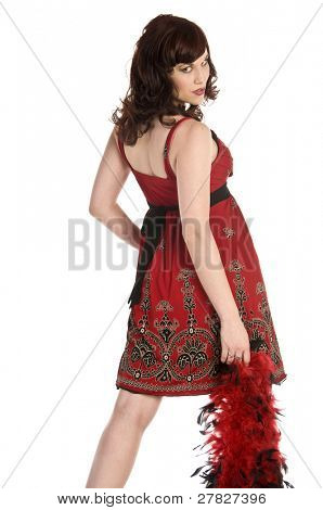 Beautiful young retro woman modeling in a red paisley print dress with a feather boa and looking back over her shoulder