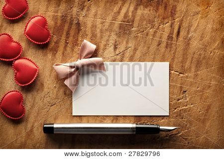 Blank visit (gift) card on old wooden table with fountain pen, small pink bow and red hearts.