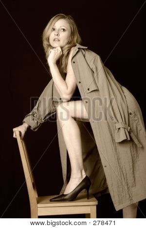 Attractive Lady With Leg On Chair Wearing Only A Trenchcoat