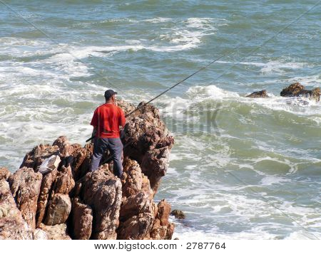 Fisherman On Rocks